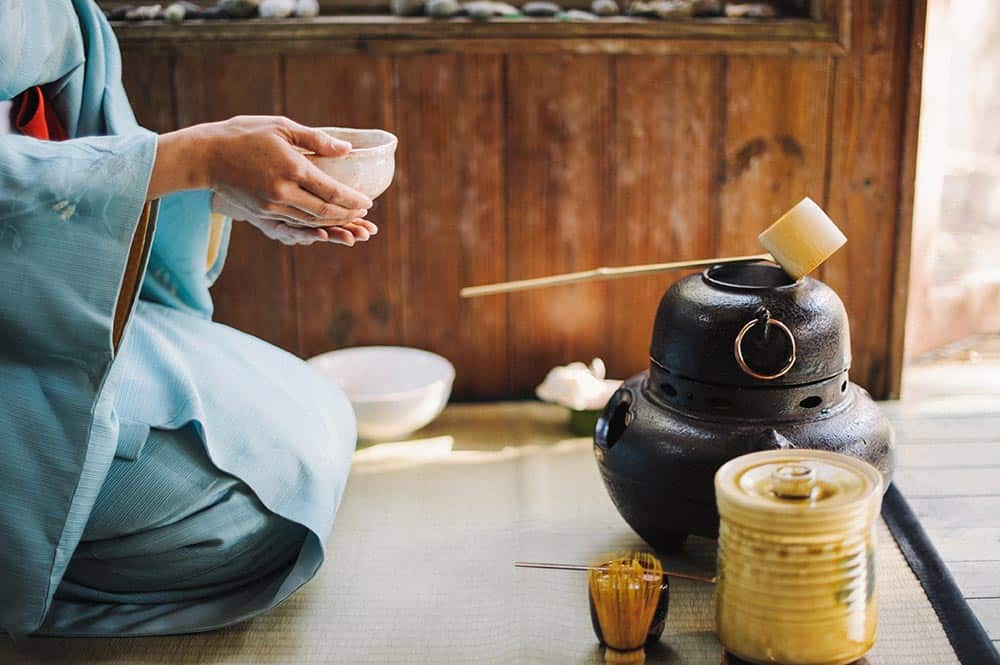A woman abides by Japanese etiqutte while drinking traditional tea.