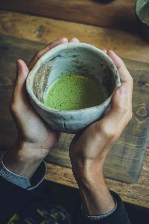 A cup of matcha tea being held in two hands.